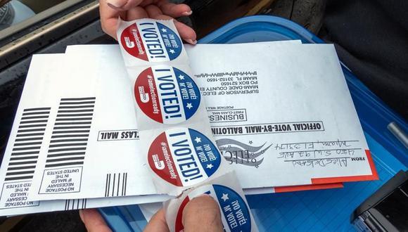 """Una persona distribuye unas pegatinas que dicen """"Yo voté"""", que se entregan a los ciudadanos tras votar en la puerta de un centro de sufragio en Miami, Florida. (EFE/Giorgio Viera)."""