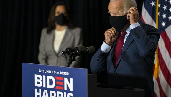 El candidato presidencial demócrata Joe Biden se coloca su mascarilla tras hablar el jueves 13 de agosto de 2020 en el hotel DuPont en Wilimington, Delaware. Al fondo está su compañera de fórmula, la senadora Kamala Harris. (AP Foto/Carolyn Kaster).