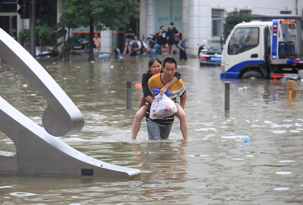 A man leads a woman on a flooded road after a recorded downpour in Zhengzhou.  (EFE / EPA / FEATURECHINA CHINA).