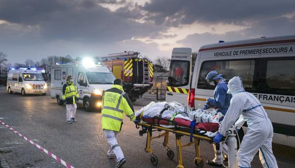 Personal médico de emergencia transporta a un paciente afectado por coronavirus (Covid-19) desde un hospital militar a una ambulancia en Mulhouse, este de Francia. (Foto de SEBASTIEN BOZON / AFP).