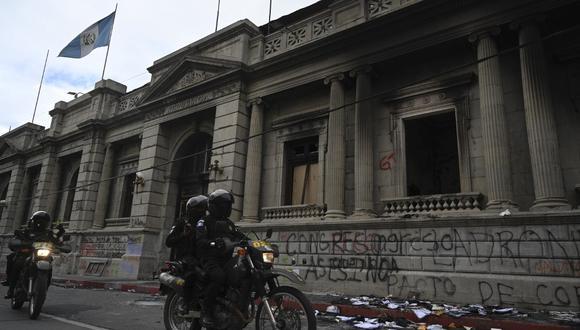 La policía circula frente al Congreso de Guatemala luega de que fuera quemado durante una protesta para exigir la renuncia del presidente Alejandro Giammattei. (Johan ORDONEZ / AFP)