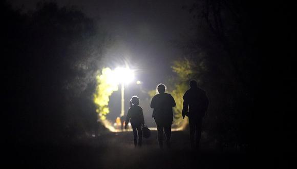Una niña hondureña de siete años (izq) camina junto a su compatriota Fernanda Solís, de 25, y a un hombre no identificado hacia un centro de procesamiento de migrantes que cruzaron la frontera ilegalmente en Mission, Texas, el 21 de marzo del 2021. (AP Photo/Julio Cortez).