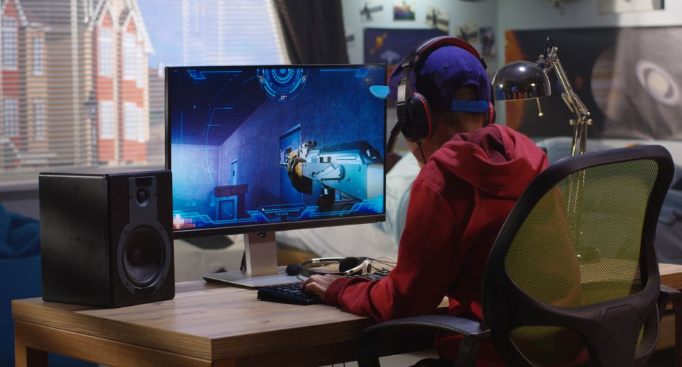 Medium shot of a boy playing with a first-person shooter video game