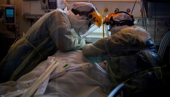 Trabajadores de la salud revisan a un paciente en una Unidad de Cuidados Intensivos (UCI) coronavirus Covid-19 en un hospital privado de Montevideo, Uruguay, el 20 de abril de 2021. (Foto de Pablo PORCIUNCULA / AFP).