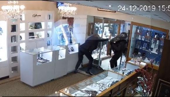 El dramático momento en que el dueño de una joyería intenta a toda cosa evitar que un ladrón ingrese a robar a su local| Foto: Captura de video YouTube