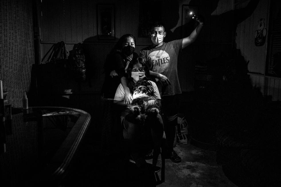 """La familia Poma vive en el asentamiento humano 23 de enero, más conocido como """"El Mirador """", en San Juan de Miraflores, y constantemente luchan por poder mantener una tensión de luz adecuada. Está conformada por Jesús, Reina (madre e hija) y Oso. (Foto: César Campos / GEC)"""