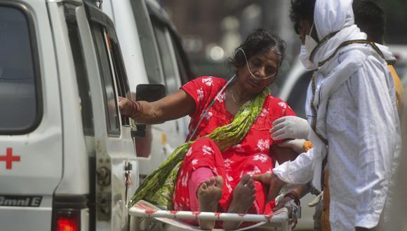 Una mujer que sufre el coronavirus Covid-19 se sienta en una camilla antes de ser ingresada en un hospital de Allahabad, en India. (Foto de SANJAY KANOJIA / AFP).