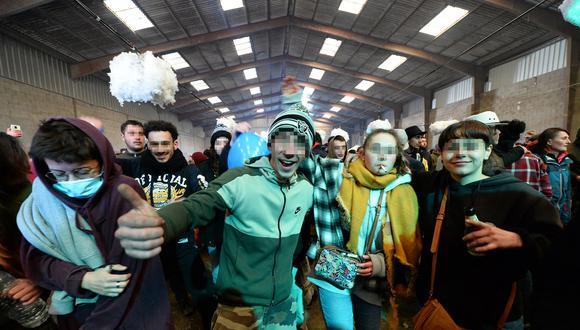 La gente posa para el fotógrafo durante una fiesta en un hangar en desuso en Lieuron a unos 40 km al sur de Rennes, el 1 de enero de 2021. (Foto: JEAN-FRANCOIS MONIER / AFP)