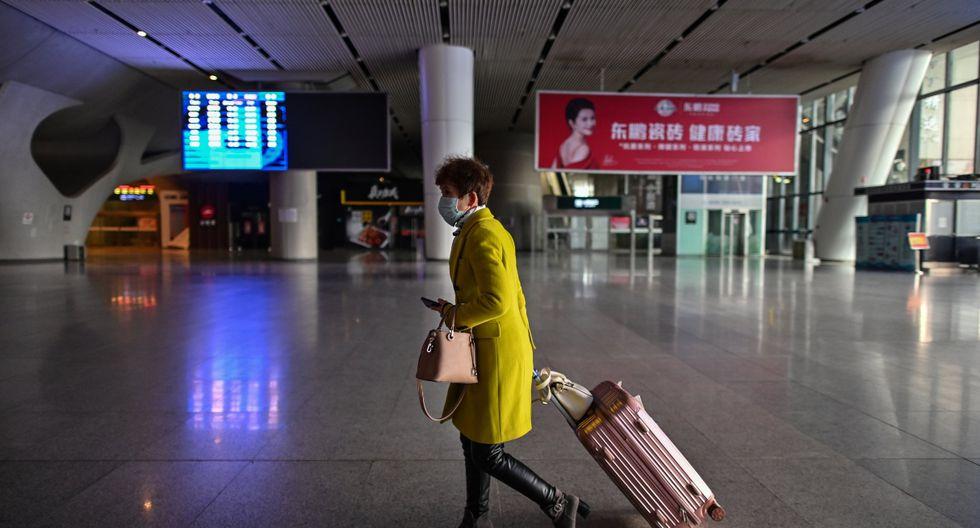 Una mujer con una máscara facial es vista en la estación de ferrocarril de Wuhan. (AFP).