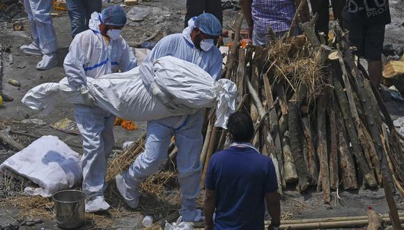 Los familiares y el trabajador de la ambulancia con equipo de protección personal (EPP) llevan los cuerpos de los pacientes que murieron por el coronavirus en un crematorio en Nueva Delhi, el 27 de abril de 2021. (Prakash SINGH / AFP).