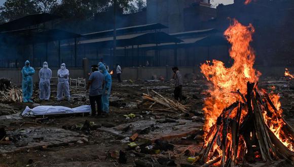 Familiares con trajes de equipo de protección personal se encuentran cerca del cuerpo de una persona que murió por coronavirus Covid-19 en Nueva Delhi, India. (Prakash SINGH / AFP).