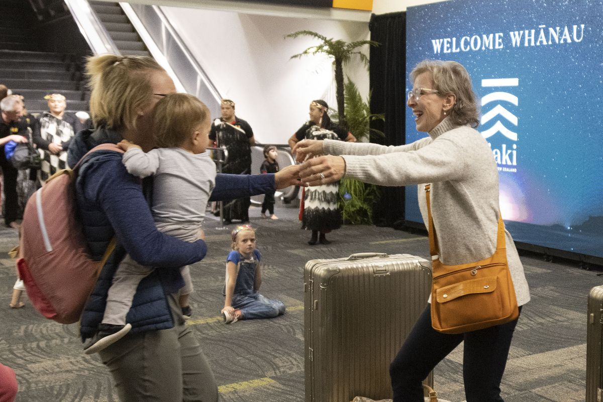 A family reunites after the arrival of the first flight from Sydney to New Zealand. (Photo by Marty MELVILLE / AFP).