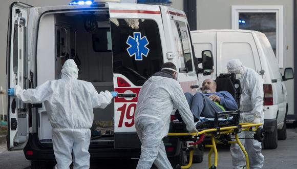 Personal médico lleva a un paciente infectado con coronavirus desde una ambulancia a la Clínica Universitaria de Enfermedades Infecciosas de Skopje. (Foto de Robert ATANASOVSKI / AFP).