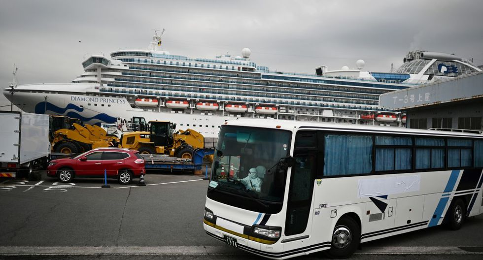 Un autobús con conductor con vestido con un equipo de protección sale del muelle junto al crucero Diamond Princess, que tiene a unas 3.600 personas en cuarentena a bordo. (AFP)
