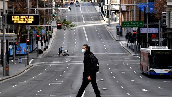 Un hombre camina por la carretera principal en el distrito comercial central de Sídney el 26 de junio de 2021, cuando la ciudad más grande de Australia entró en un bloqueo de dos semanas para contener la variante Delta del coronavirus. (Saeed KHAN / AFP).