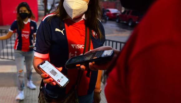 Una aficionada al fútbol muestra un código QR para controlar su inoculación y prueba negativa de coronavirus en la entrada del estadio de Cerro Porteño en Paraguay. (NORBERTO DUARTE / AFP).