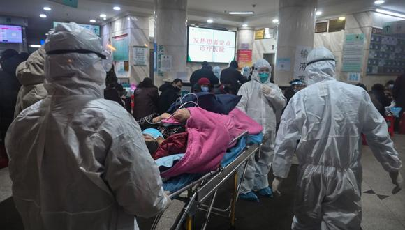 Personal médico, que usa ropa protectora para protegerse contra un coronavirus, atiende a un paciente en el Hospital de la Cruz Roja de Wuhan (Foto: AFP)