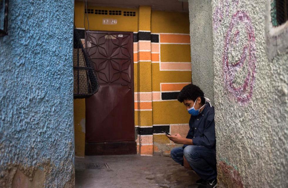 Jonathán Figueroa, de 14 años, usa su teléfono celular, conectado a la señal wifi de un vecino, frente a su casa en el barrio Bello Campo en Chacao, Caracas (Venezuela), el 6 de octubre de 2020, en medio de la pandemia de coronavirus. (AFP / Cristian Hernandez).