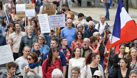 Los manifestantes sostienen pancartas y corean consignas mientras marchan durante una manifestación en Nantes, en el oeste de Francia para protestar contra el pase de salud obligatorio Covid-19 para acceder a la mayor parte del espacio público. (Foto: Sebastien SALOM-GOMIS / AFP)