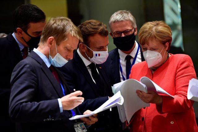El presidente de gobierno de España, Pedro Sánchez (izquierda); el presidente francés Emmanuel Macron (centro) y la canciller alemana Angela Merkel (derecha) examinan documentos durante una cumbre de la UE en Bruselas. (Foto: JOHN THYS / POOL / AFP).