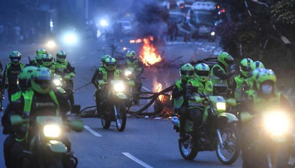 La policía en motocicletas interviene en los enfrentamientos después de que los manifestantes bloquearan una carretera durante una nueva protesta antigubernamental en Medellín, Colombia. (Foto: AFP / JOAQUIN SARMIENTO).