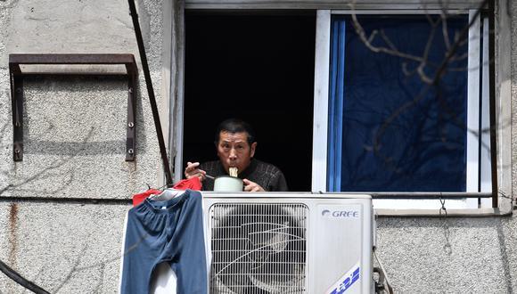 Un habitante de Wuhan que está en cuarentena por el coronavirus mira desde la ventana de su vivienda. (Reuters).