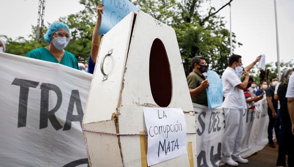 """Personal de la salud protesta con ataúdes simbólicos con el mensaje """"La corrupción mata"""" para denunciar la falta de medicamentos y recursos para combatir el covid-19, frente al Hospital de Clínicas en San Lorenzo (Paraguay). (Foto: EFE)"""