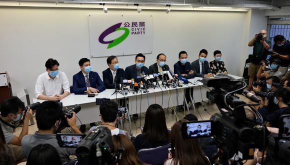 El líder del Partido Cívico, Alvin Yeung, en el centro, se une a otros miembros de su partido durante una conferencia de prensa en Hong Kong, después de que una docena de activistas locales de la democracia fueran descalificados para participar en las elecciones legislativas de septiembre. (Anthony WALLACE / AFP)