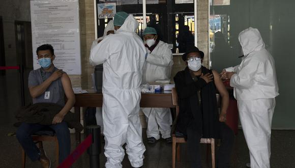 Imagen referencial en la que se ve a galenos aplicar las dosis de vacuna contra el coronavirus. AP