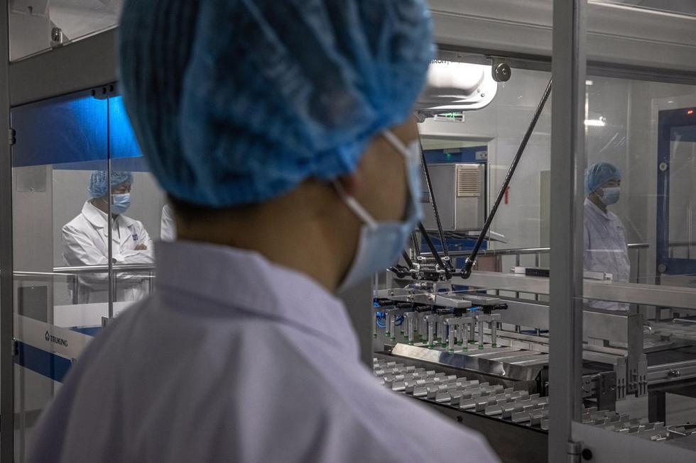 El presidente de la farmacéutica estatal china Sinopharm, Liu Jingzhen, anunció este viernes que la compañía prevé producir este año 1.000 millones de dosis de su vacuna inactivada contra el coronavirus, una buena parte de ellas destinadas a la exportación. Imagen de trabajadores en el taller de envasado en Beijing. (Texto: EFE / Foto: AFP)