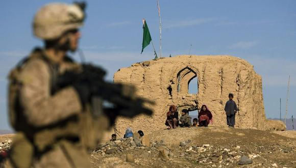 Niños afganos observan como un infante de marina estadounidense patrulla en el pequeño pueblo de Delaram en la provincia de Nimroz, en el sur de Afganistán, el 6 de enero de 2010. (Reuters).