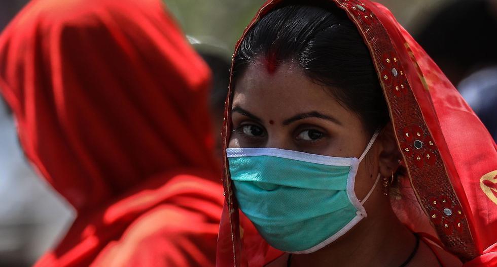 Dos mujeres llevan mascarillas en la entrada del Hospital Indira Gandhi en Bombay, India, donde esperan para conseguir un pase para viajar dentro de las restricciones de movilidad instauradas en el país debido al coronavirus. (EFE/ Divyakant Solanki).