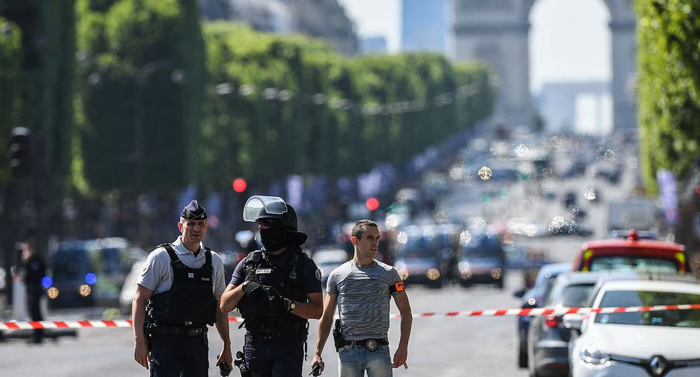 Policemen stand guard, on June 19, 2017 on the Champs-Elysees avenue in Paris, after a car crashed into a police van before bursting into flames, with the driver being armed, probe sources said.   / AFP / ALAIN JOCARD