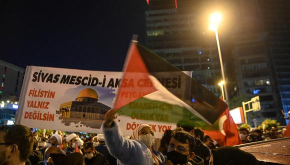 """Los manifestantes sostienen banderas nacionales de Palestina y Turquía y corean consignas que dicen """"Palestina, no estás solo"""" durante una manifestación contra Israel frente al Consulado de Israel en Estambul el 9 de mayo de 2021.  (Foto: Ozan KOSE / AFP)"""