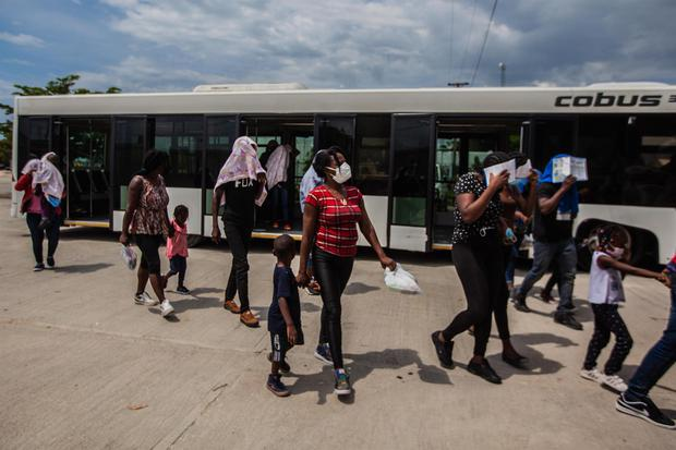 Haitian migrants deported from the United States walk with their children after alighting from a plane at Toussaint Louverture airport in Port-au-Prince.  (EFE / Richard Pierrin).