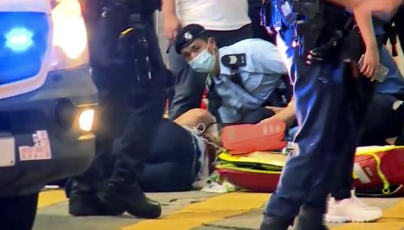 Un oficial de policía en el suelo recibe tratamiento médico luego de ser apuñalado por un hombre en una calle de Causeway Bay de Hong Kong, el jueves 1 de julio de 2021. (TVB/AP).