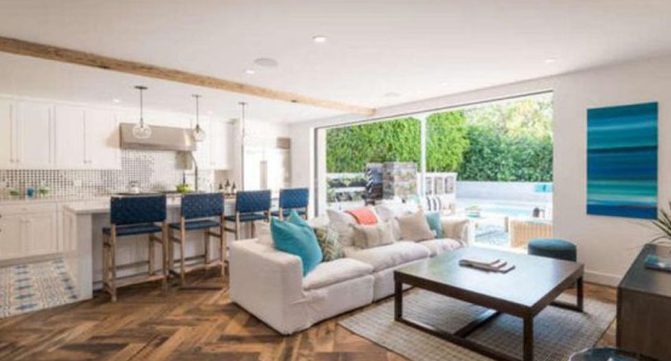 El color blanco sobresale en las paredes y los muebles de cocina. La barra delimita la cocina de la sala, donde también destacan cuadros, cojines y sillas en tonos azules. (Foto: themls.com)