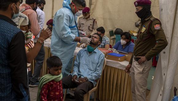 Un enfermero toma una muestra nasal de un pasajero en una prueba de COVID-19 en una terminal de ómnibus en Nueva Delhi, India, miércoles 24 de marzo de 2021. (AP Foto/Altaf Qadri).