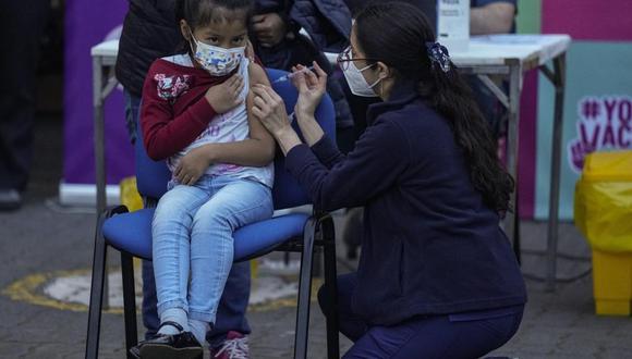 Una trabajadora de la salud inocula a una niña contra el coronavirus COVID-19 en la escuela Providencia en Santiago de Chile, el lunes 27 de septiembre de 2021. (AP Foto/Esteban Felix).