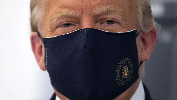 El presidente de Estados Unidos, Donald Trump, usa mascarilla mientras recorre un laboratorio donde fabrican componentes para una posible vacuna contra el coronavirus Covid-19. (Foto de JIM WATSON / AFP).