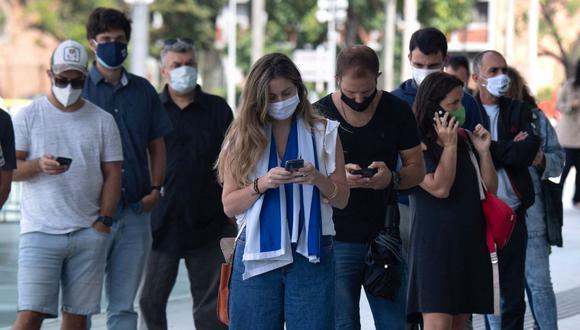 Una mujer con una bandera uruguaya al hombro hace fila con otras para ser vacunadas contra el coronavirus en Montevideo, Uruguay. (Foto Pablo PORCIUNCULA / AFP).
