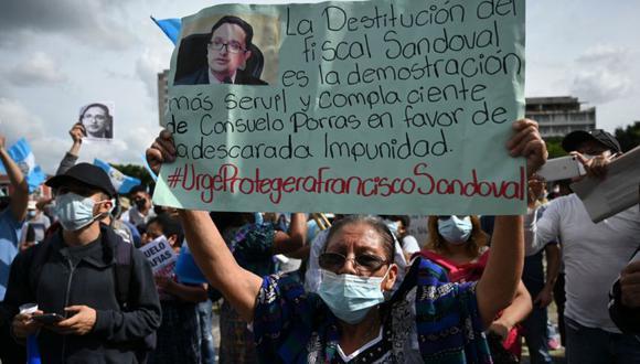 """Un manifestante sostiene un cartel que dice """"La destitución del fiscal Sandoval es la prueba servil y complaciente de que Consuelo Porras está a favor de la impunidad desvergonzada"""" durante una protesta para exigir la renuncia del presidente guatemalteco Alejandro Giammattei. (Foto: Johan ORDONEZ / AFP)"""