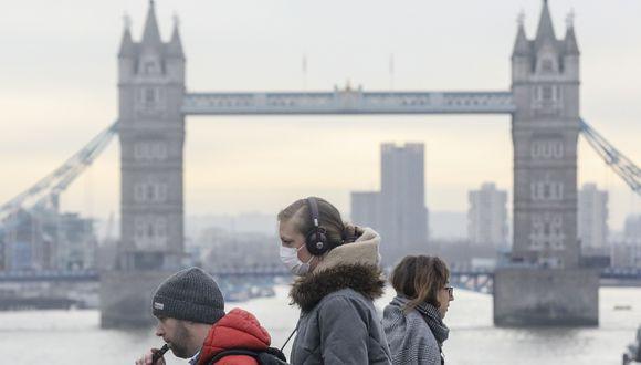 Un grupo de personas que usa máscara facial protectora contra el coronavirus camina sobre el Puente de Londres, en el Reino Unido. (Simon Dawson / Bloomberg).