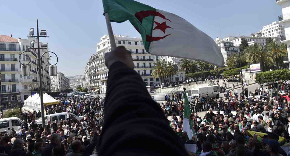 Los argelinos ondean la bandera nacional mientras demuestran que exigen un cambio radical en todo el sistema político del país. (Foto: AFP)