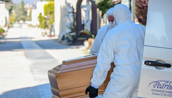 Trabajadores que usan una máscara para protegerse del coronavirus descargan un ataúd en el cementerio monumental de Bérgamo, Lombardía, mientras los entierros de las personas que murieron por Covid-19 se llevan a cabo a ritmo de uno cada media hora. (AFP / Piero Cruciatti).