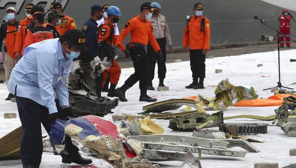 Un investigador del Comité Nacional de Seguridad del Transporte de Indonesia (KNKT) inspecciona los escombros encontrados en las aguas alrededor del lugar donde se estrelló el avión de pasajeros de Sriwijaya Air. (Foto AP / Achmad Ibrahim).