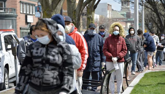 La gente espera en la fila para que la Guardia Nacional distribuya alimentos a algunas comunidades de Massachusetts más afectadas por la pandemia de coronavirus. (Foto: AFP/Joseph Prezioso)