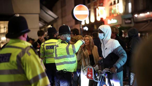 La policía observa cómo la gente se festeja en una calle del Soho, mientras se alivian las restricciones de la enfermedad por coronavirus (COVID-19), en Londres, Reino Unido, el 12 de abril de 2021. (REUTERS/Henry Nicholls).
