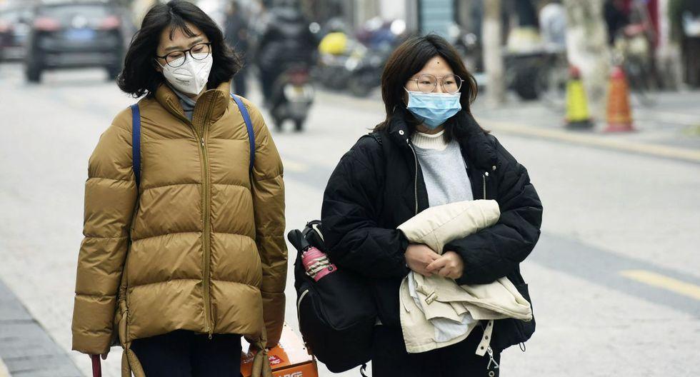 Las mujeres usan máscaras mientras caminan por una calle en Hangzhou, en la provincia oriental china de Zhejiang. (AP).