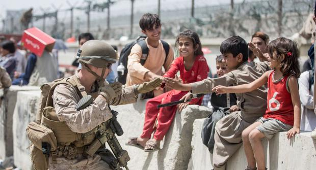 In this film, a Marine plays with children waiting to be processed during an evacuation at the Hamid Karzai International Airport in Kabul, courtesy of the U.S. Federal Command Public Affairs Department.  (Photo: Samuel Ruiz / US Federal Command Public Affairs / AFP).
